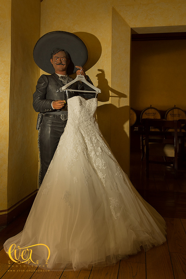 mariachi charro holding wedding dress bride wedding dress at hacienda casa cuervo, tequila jalisco Mexico